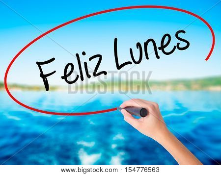 Woman Hand Writing Feliz Lunes (happy Monday In Spanish) With A Marker Over Transparent Board