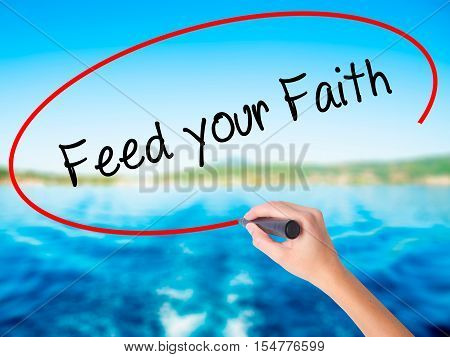 Woman Hand Writing Feed Your Faith With A Marker Over Transparent Board