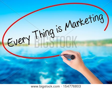 Woman Hand Writing  Every Thing Is Marketing With A Marker Over Transparent Board