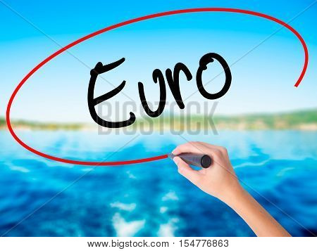 Woman Hand Writing Euro With A Marker Over Transparent Board