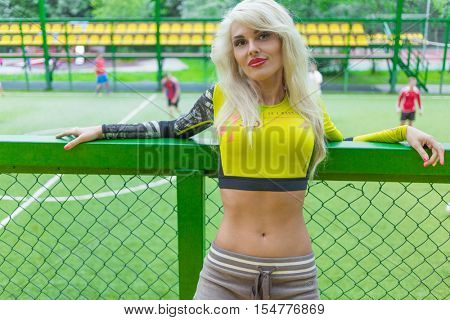 MOSCOW - JUL 16, 2015: Beautiful blonde woman with long hair in top leaned on fence on soccer field