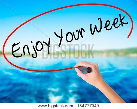 Woman Hand Writing Enjoy Your Week With A Marker Over Transparent Board