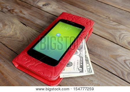 Mobile banking, SMS banking . Payment by phone. The concept of mobile banking - phone and purse with money, dollars as a whole. The latest technology.
