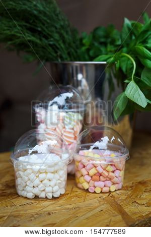 Desserts choice. Marshmallow chewing candies in glass jars on counter bar for sale. Traditional american sweets for sale, closeup, vertical