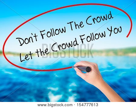 Woman Hand Writing Don't Follow The Crowd Let The Crowd Follow You With A Marker Over Transparent Bo