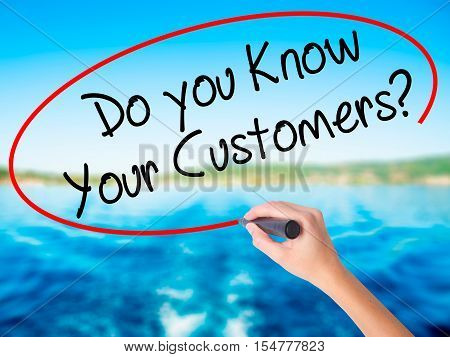 Woman Hand Writing Do You Know Your Customers? With A Marker Over Transparent Board