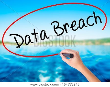 Woman Hand Writing Data Breach With A Marker Over Transparent Board