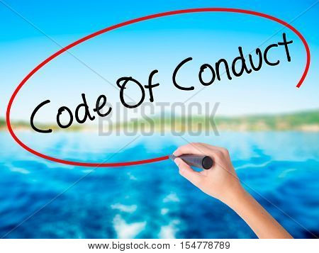 Woman Hand Writing Code Of Conduct With A Marker Over Transparent Board