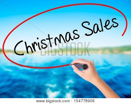 Woman Hand Writing Christmas Sales With A Marker Over Transparent Board