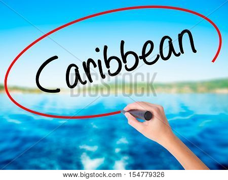 Woman Hand Writing Caribbean With A Marker Over Transparent Board