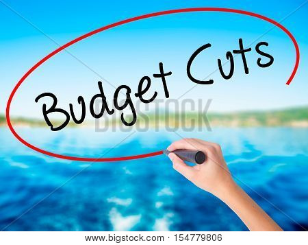 Woman Hand Writing Budget Cuts With A Marker Over Transparent Board