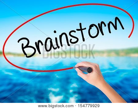Woman Hand Writing Brainstorm With A Marker Over Transparent Board.