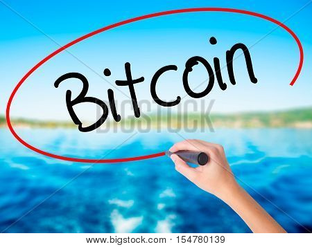 Woman Hand Writing Bitcoin With A Marker Over Transparent Board.