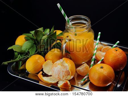 tangerine juice with fresh tangerines on a black background