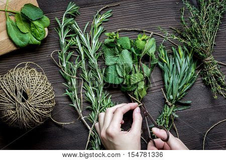 bundle of sage and thyme, mint, rosemary estragon on wooden background with hands top view.