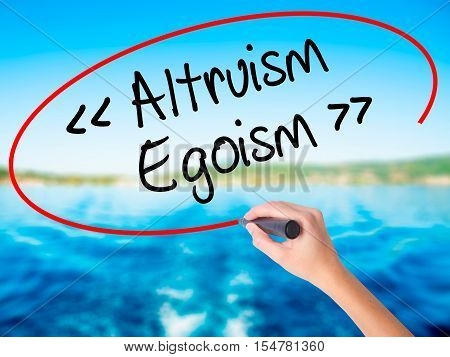 Woman Hand Writing Altruism - Egoism With A Marker Over Transparent Board.