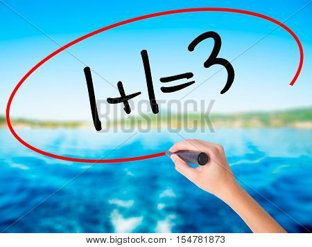 Woman Hand Writing 1+1=3 With A Marker Over Transparent Board