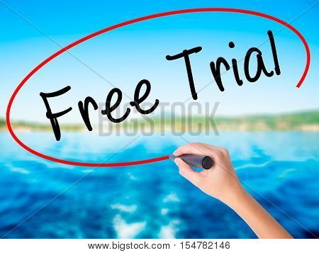 Woman Hand Writing Free Trial With A Marker Over Transparent Board