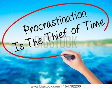Woman Hand Writing  Procrastination Is The Thief Of Time With A Marker Over Transparent Board