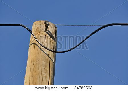 Closeup of a dangerous electric cable on a wooden pylon and the clear sky