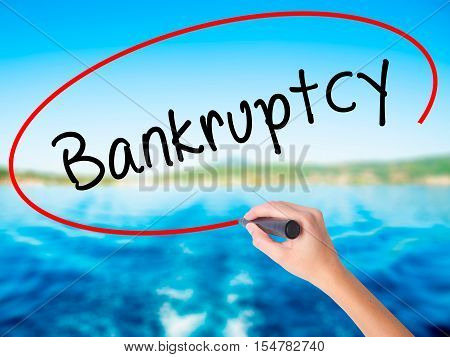 Woman Hand Writing Bankruptcy With A Marker Over Transparent Board