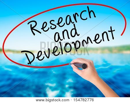 Woman Hand Writing Research And Development With A Marker Over Transparent Board