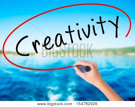 Woman Hand Writing Creativity With A Marker Over Transparent Board