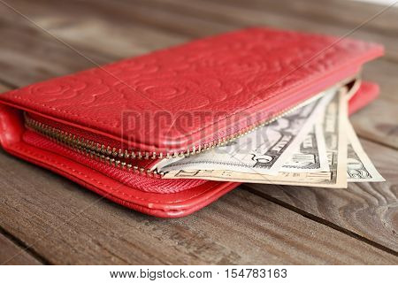 Female red wallet with money on a dark wooden background.The concept of cost of money.