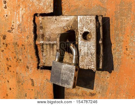 Padlock, new metal padlock on rust background, grunge padlock, metal door