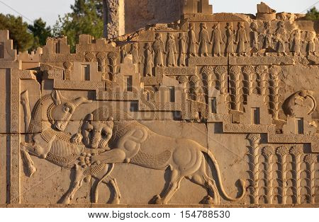 Embossed bas relief carving of a lion hunting a bull on one of the staircases in Persepolis UNESCO World Heritage Site near Shiraz belonging to Achaemenid Empire 500 BC.