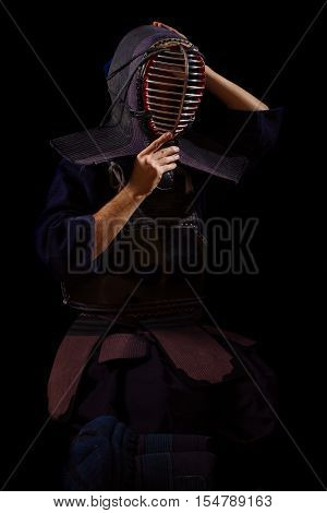 Kendo warrior in traditional uniform on a black background