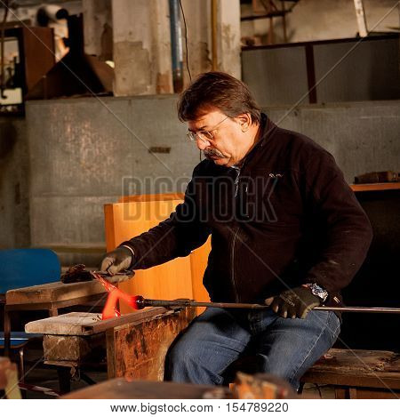 Murano island Venice Italy - October 29 2012: Glassblowing artisan at work in a crystal glass workshop in Murano island Venice Italy. Murano glassmakers use the same tools as their ancestors have thousands of years ago