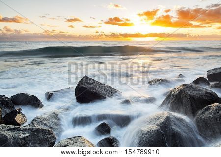 Sunrise with ocean wave and water cascading over the rocks at Burleigh Headland