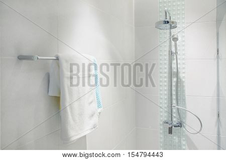 Interior of bathroom with modern shower head and white towel at rail in bathroom.