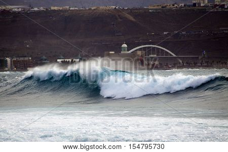 ocean wave breaking by Confital beach north East of Gran Canaria October 2016 Auditorio in the background