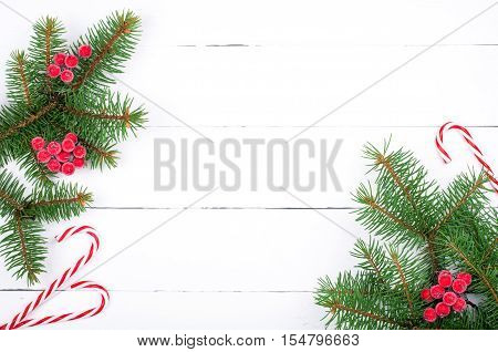 Christmas tree branch with decorations and candy canes on white wooden table. Christmas background. Copy space. Top view