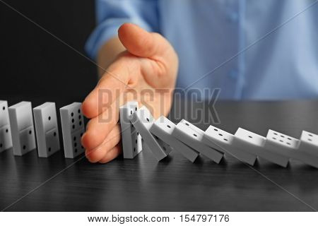 Businesswoman hand trying to stop toppling dominoes on table poster