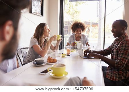 Five adult friends sitting in a cafe, over shoulder view