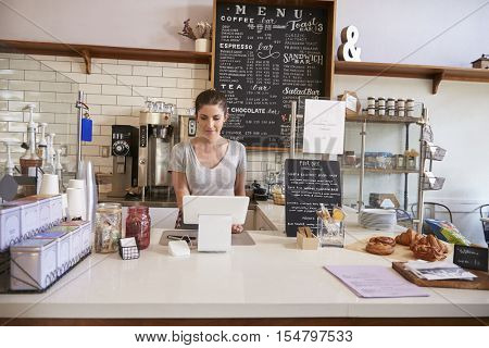 Woman working on the till at the counter of a coffee shop