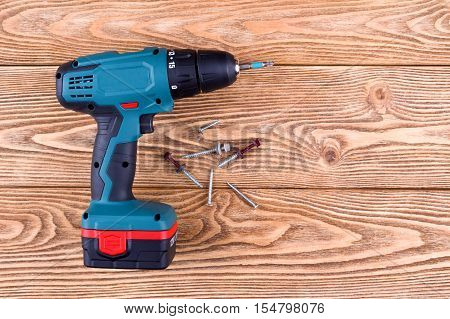 Cordless drill with screws on a wooden background
