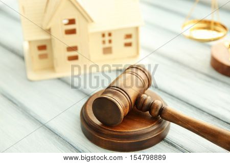 Gavel and miniature house on wooden background. Auction concept