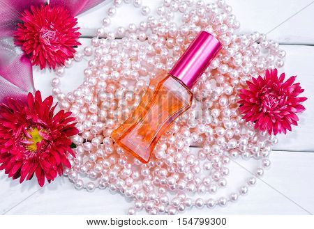 Red glass perfume bottle, pink pearl beads, aster flowers, silk textile on a painted white wooden background. Floral aroma and femininity concept.