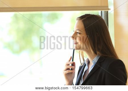 Side view of a businesswoman wearing suit thinking and looking outdoors through a window at office