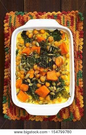 Baked pumpkin kale and chickpea casserole with pumpkin seeds on top in casserole dish photographed with natural light (Selective Focus Focus on the top of the casserole)