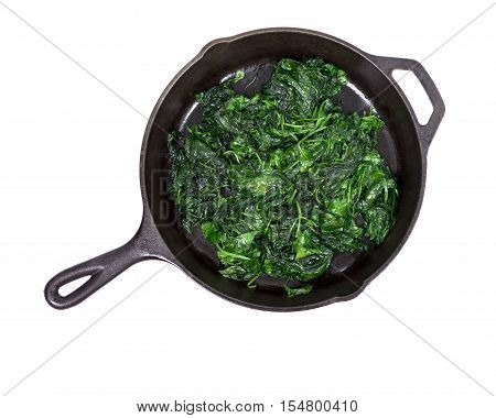 Sauteed fresh organic baby spinach in cast iron skillet isolated on white background