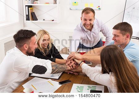 Team put hands together, show connection and alliance. Teambuilding in the office, young businessmen and women in casual unite hands for teamwork and cooperation at new project.