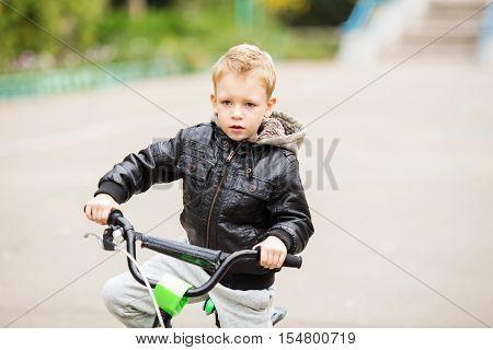Portrait Of Adorable Little Urban Boy Wearing Black Leather Jacket.