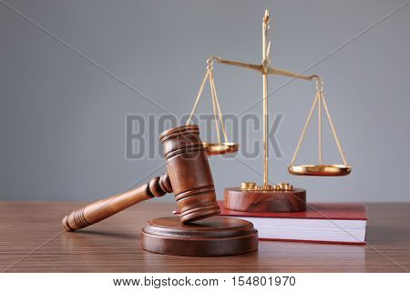 Judge's gavel with book and justice scales on wooden table and grey background