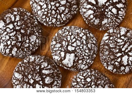 Chocolate crinkle cookies traditional American Christmas cookies photographed overhead on wooden plate with natural light