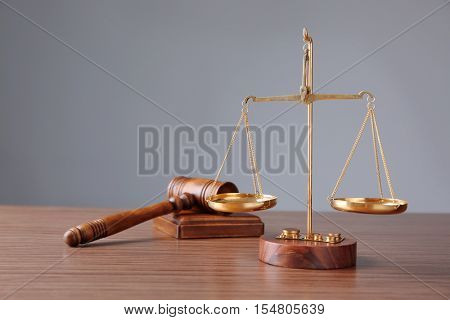 Justice scales and judge's gavel on wooden table and grey background